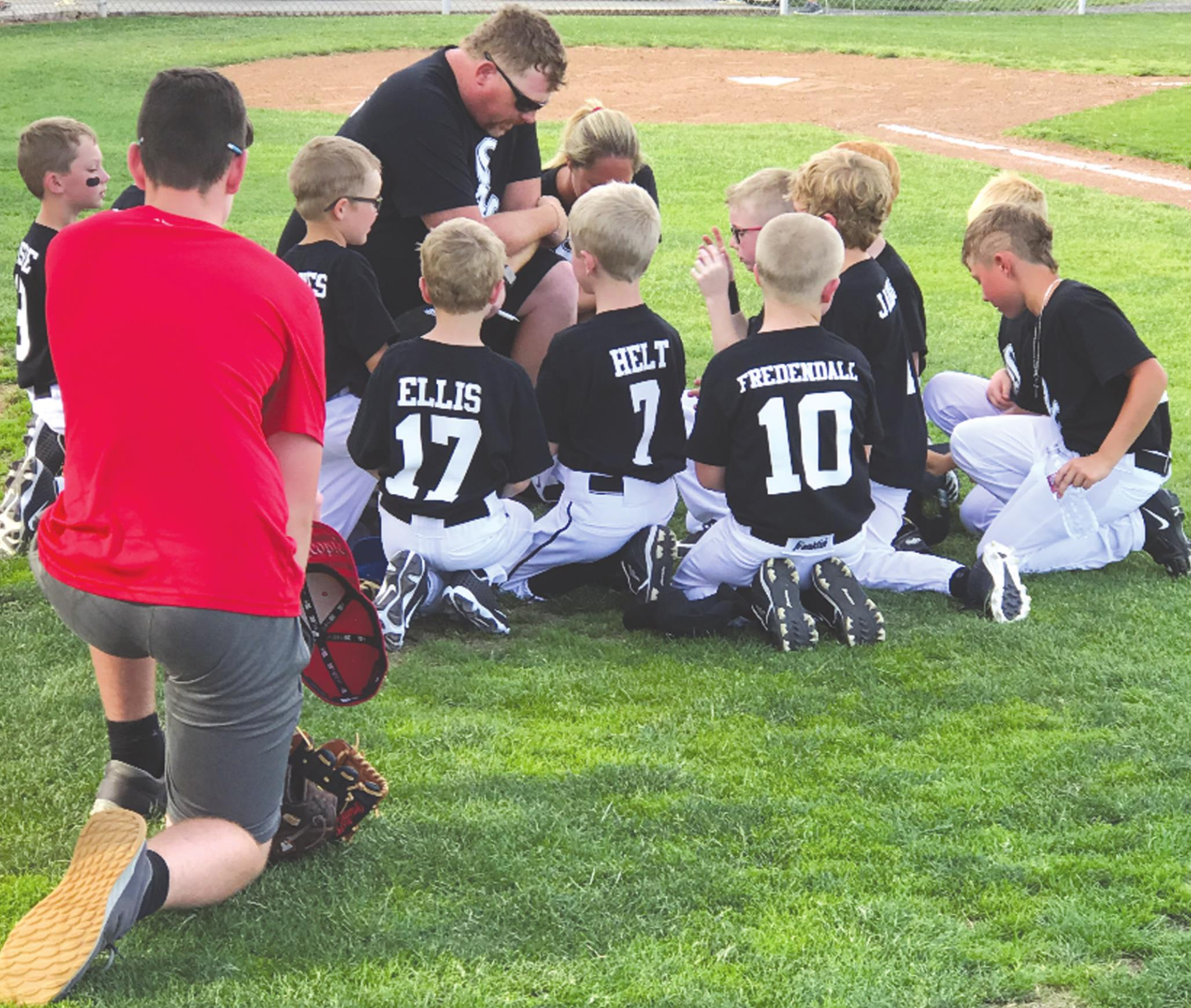 Matt and Kaye Frye, center, lead their coach pitch team in a prayer before the a game. The Frye's son, Weston, plays on the team. Their daughters, Joeclyn and Piper, play on a T-ball team. Provided