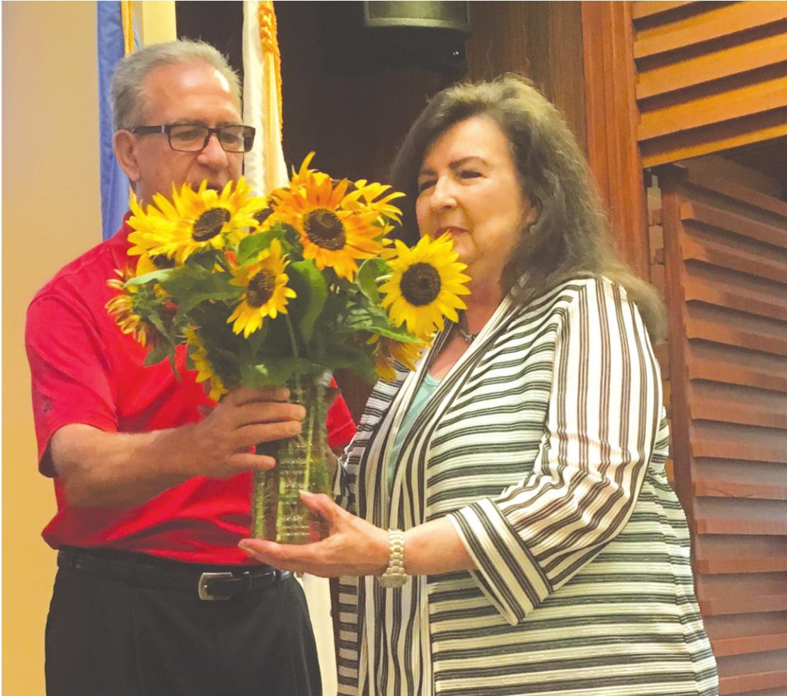 Josh Burton/WDN At right, Mayor Mike Brown honors Callie Waldrop at Friday's Weatherford City Commission meeting. The mayor gave Waldrop sunflowers from the community garden in Weatherford.